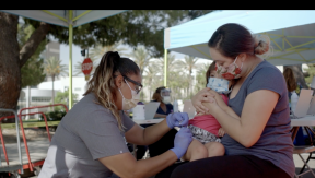 Nurse administers vaccine to child on mother's lap